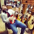 Гитарист, магазин музыкальных инструментов