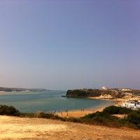 Photo taken at Praia de Vila Nova de Milfontes by Joana P. on 7/16/2013