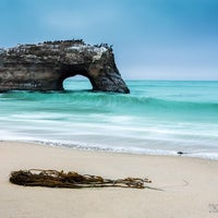 Photo taken at Natural Bridges State Beach by Tass A. on 7/29/2013
