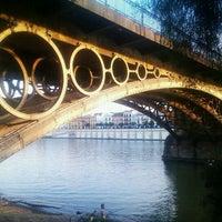 Photo taken at Isabel II Bridge 'Triana Bridge' by Jessica C. on 3/22/2012