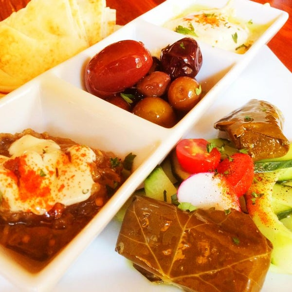 Start with the Mediterranean Sampler - Hummus, Baba Guanoush, Stuffed Grape Leaves, Fresh Cucumber, Mixed Olives, Pita Bread