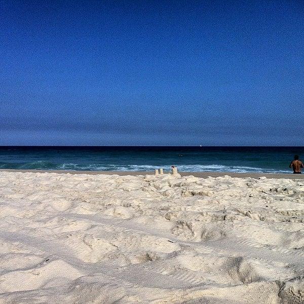 Photo taken at Praia da Barra da Tijuca by Denise on 6/8/2013
