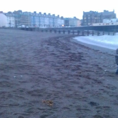 Photo taken at Aberystwyth Beach by Kevin D. on 2/11/2013