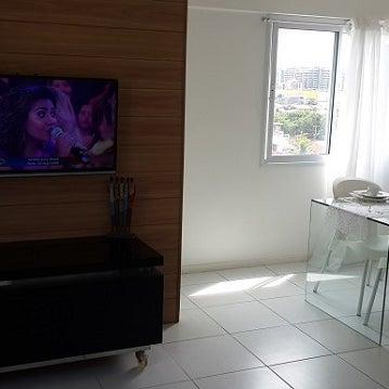 Sala com TV Led, mesa de vidro e sofá-cama.