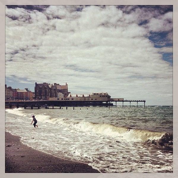 Photo taken at Aberystwyth Beach by Slynky C. on 8/11/2013